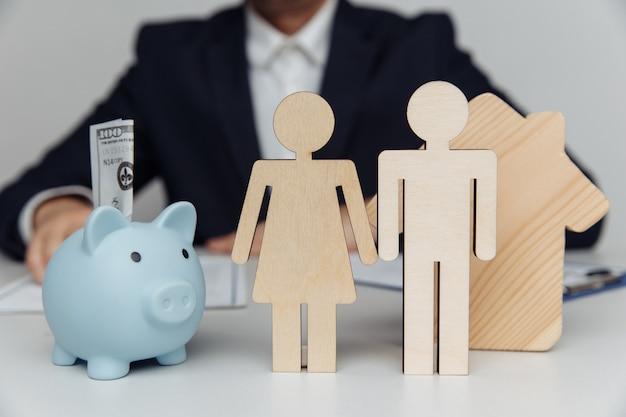 Corretor por trás de figuras de família jovem e compra de cofrinho ou conceito de hipoteca