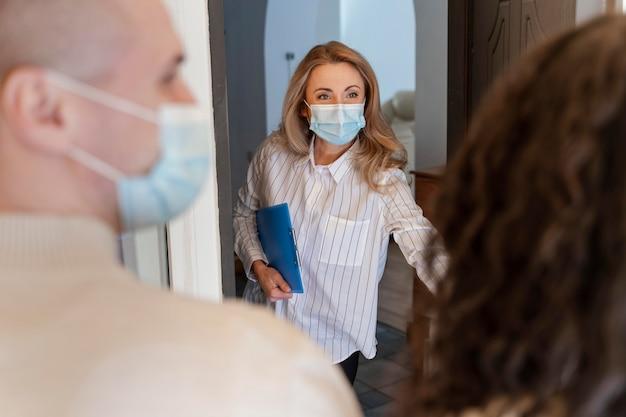 Corretora de imóveis com máscara médica convidando casal para ver a nova casa