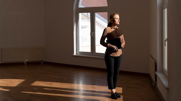 Corretora de imóveis em uma casa vazia e olhando pela janela com espaço de cópia
