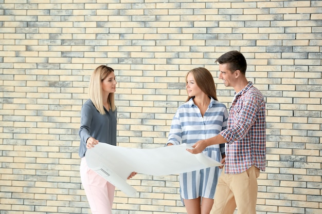 Corretora de imóveis mostrando plano de novo apartamento aos clientes