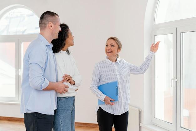 Corretora de imóveis sorridente mostrando a casa vazia para um jovem casal