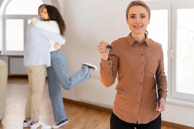 Corretora de imóveis sorridente segurando novas chaves de casa com um casal se abraçando ao fundo