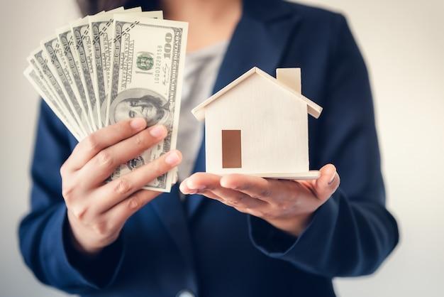 Corretora de venda de imóveis, mostrando dinheiro e modelo de casa ao cliente.