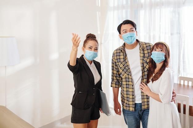 Corretora imobiliária vietnamita mostrando a nova casa para um jovem casal com máscara médica