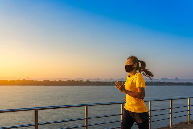 Corrida asiática bonita da aptidão nova bonita e exercício que veste uma máscara protetora no riverwalk na manhã.