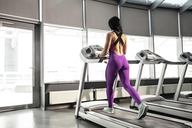 Corrida. jovem mulher caucasiana muscular praticando no ginásio com cardio. modelo feminino atlético fazendo exercícios de velocidade, treinando a parte inferior e superior do corpo. bem-estar, estilo de vida saudável, musculação.