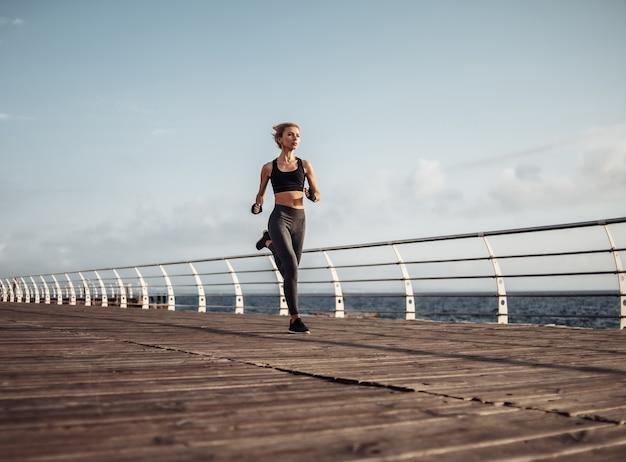 Corrida matinal. jovem mulher atlética em roupas esportivas corre na praia ao nascer do sol