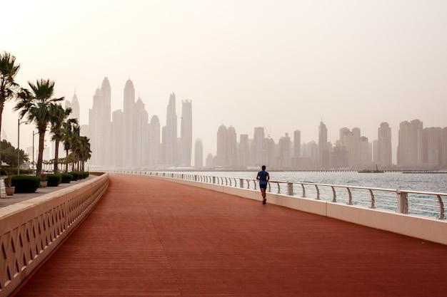 Corrida matinal, um homem corre ao longo da estrada com uma bela vista de dubai.
