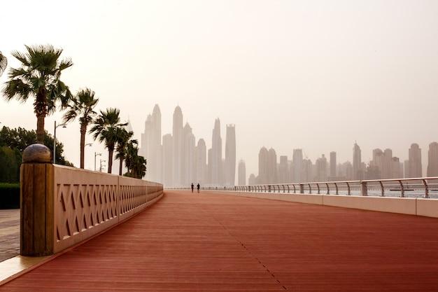 Corrida matinal, um homem e uma mulher correm pela estrada com uma bela vista de dubai. emirados árabes unidos