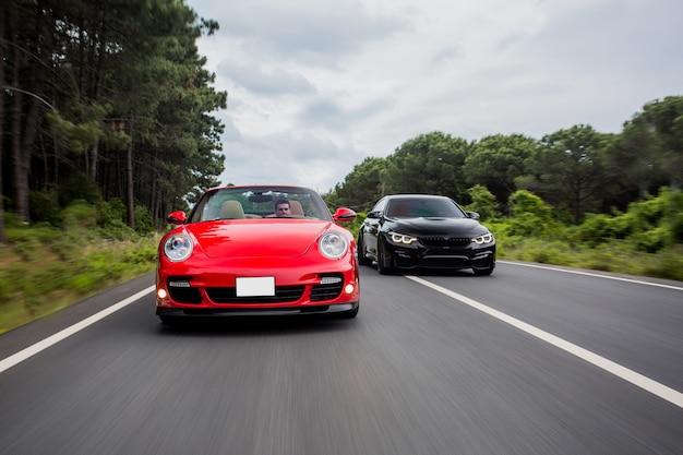 Corrida na estrada entre carros cupê preto e vermelho.