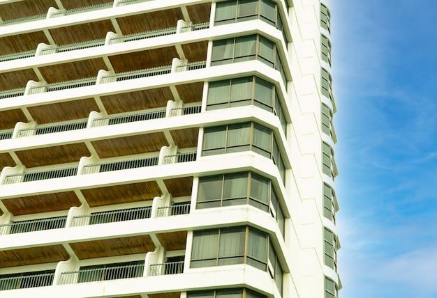 Corrimão de aço da varanda do hotel contra edifício residencial contra fundo de céu azul