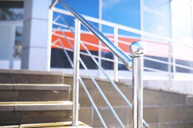 Corrimão em vidro e aço inoxidável. escadas no interior moderno. corrimão de vidro. vista de baixo ângulo das escadas que conduzem ao edifício moderno.