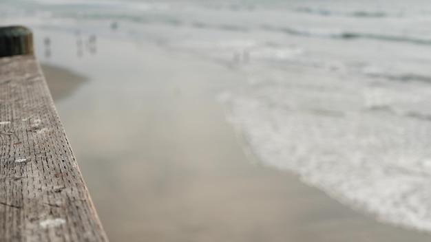 Corrimãos do cais de madeira, calçadão à beira-mar, praia da califórnia, eua. oceano desfocado, ondas do mar.