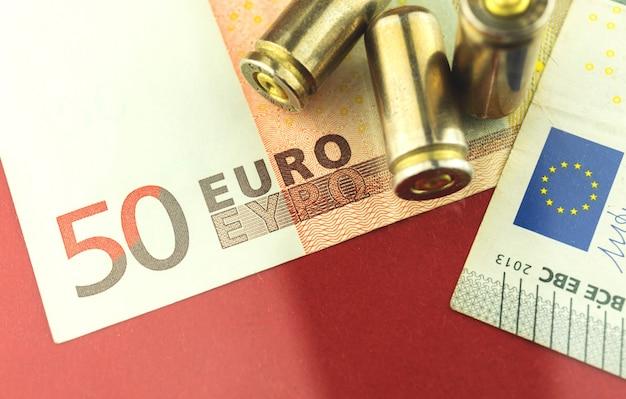 Corrupção na europa, dinheiro do euro e bala na foto do conceito de fundo, perigo e munições
