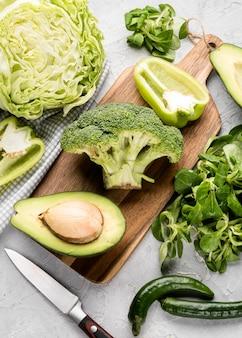Corta vários vegetais verdes com abacate