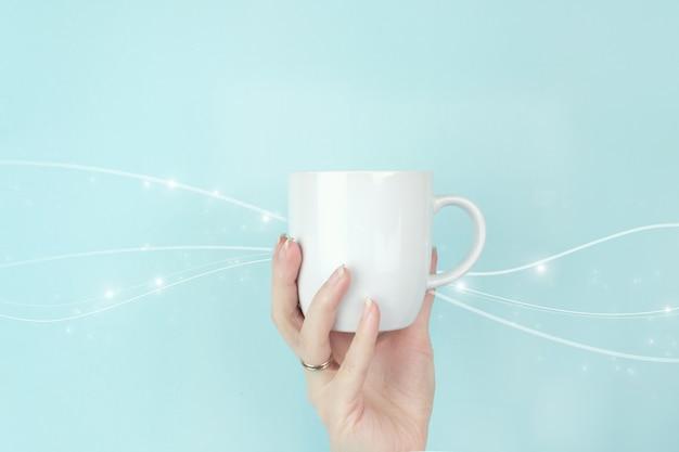 Cortada a exibição de uma mão feminina com uma xícara de café branca e uma onda digital sobre fundo azul.