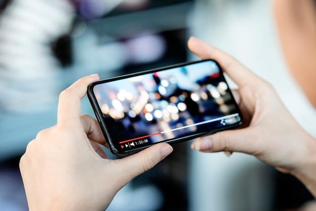 Cortada a imagem da mão feminina segurando o smartphone e assistir vídeo enquanto em pé ao ar livre