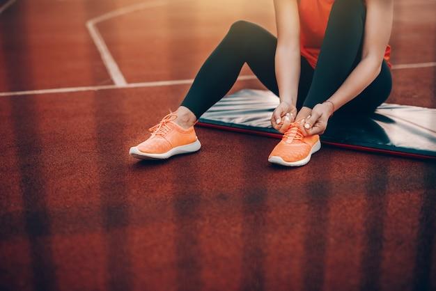 Cortada a imagem da mulher caucasiana em sportswear sentado no tatame na quadra e amarrar o cadarço.