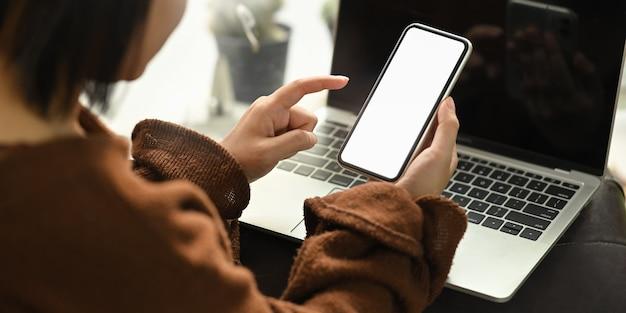 Cortada a imagem da mulher elegante, segurando a tela em branco branca móvel nas mãos enquanto está sentado na frente de seu laptop computador no sofá sobre a confortável sala de estar.