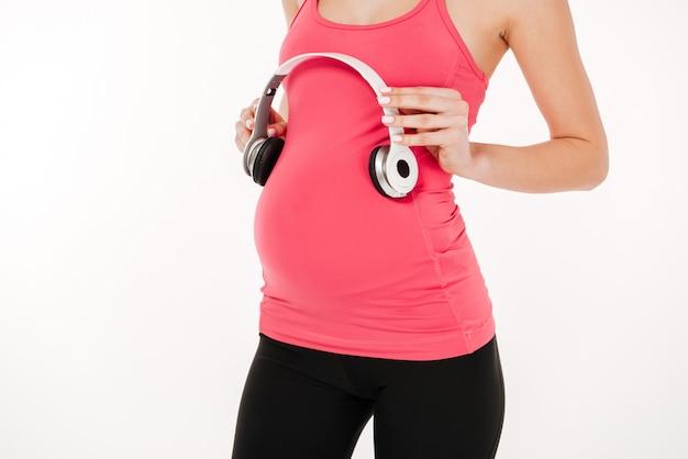Cortada a imagem da mulher grávida fitness segurando o fone de ouvido na barriga