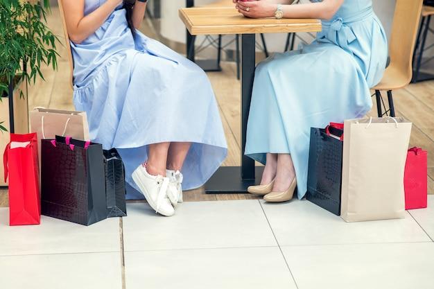 Cortada a imagem de duas namoradas, sentado à mesa com sacos de papel