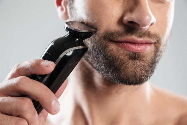 Cortada a imagem de um homem barbudo usando barbeador elétrico