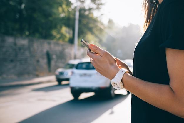 Cortada a imagem de um telefone celular em mãos femininas
