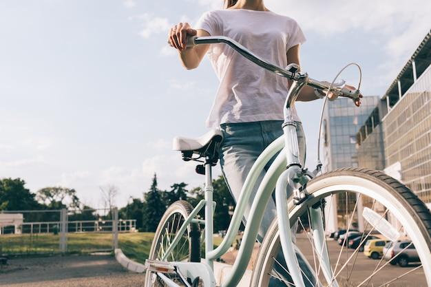 Cortada a imagem de uma jovem em jeans e uma camiseta com uma bicicleta