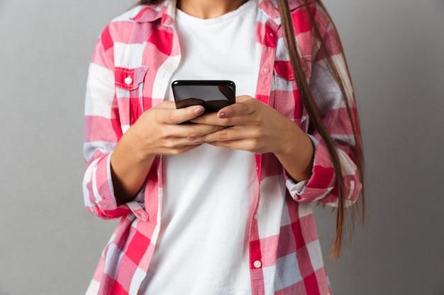 Cortada a imagem de uma jovem mulher em camisa xadrez