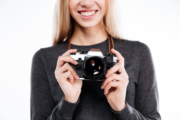 Cortada a imagem de uma menina loira sorridente segurando a câmera retro