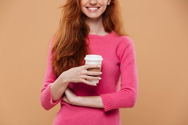 Cortada a imagem de uma menina ruiva sorridente segurando a xícara de café
