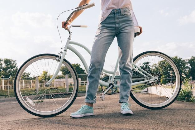 Cortada a imagem de uma mulher de jeans com uma bicicleta no parque