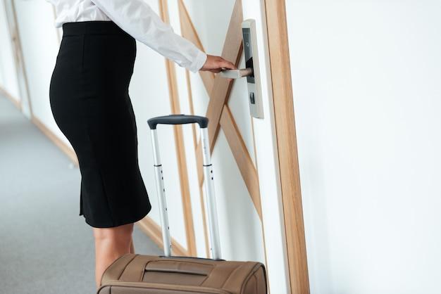 Cortada a imagem de uma mulher de negócios, puxando a maçaneta da porta