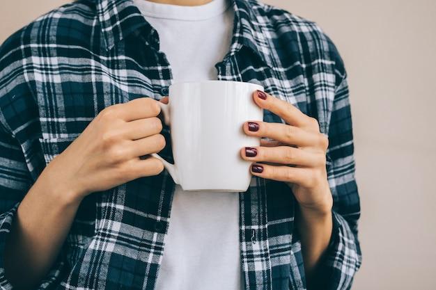 Cortada a imagem de uma mulher em uma camisa xadrez, segurando um copo branco com uma bebida