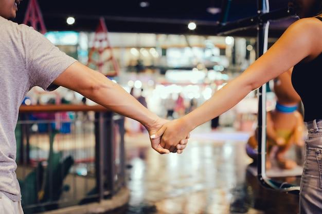 Cortada a imagem do casal segurando a mão e caminhar ao ar livre no shopping