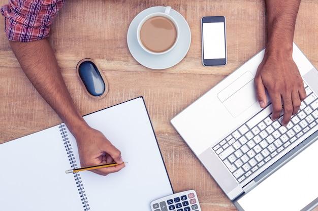 Cortada a imagem do empresário escrevendo no livro enquanto trabalha no laptop no escritório