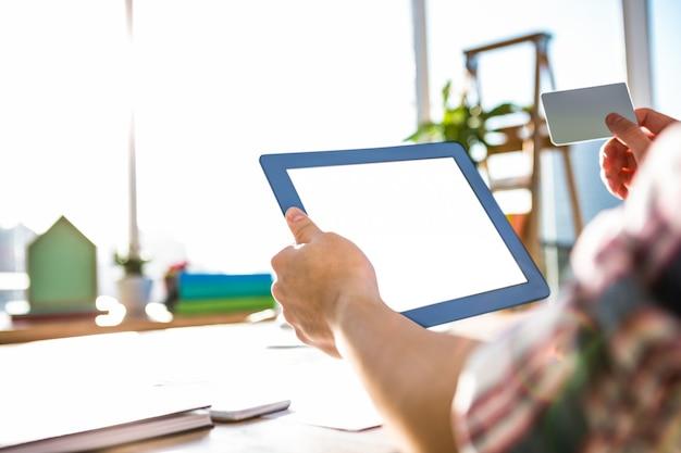 Cortada a imagem do empresário hipster usando tablet e cartão de crédito no escritório