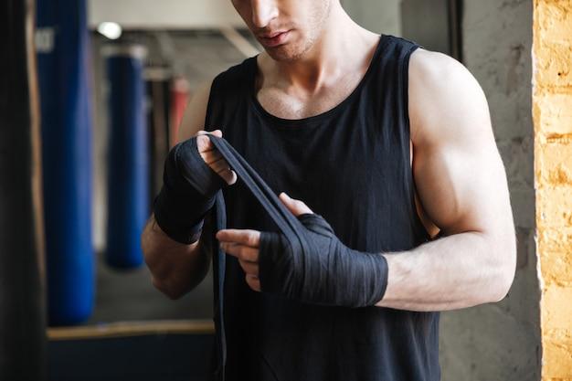 Cortada a imagem do homem usando luvas para boxe
