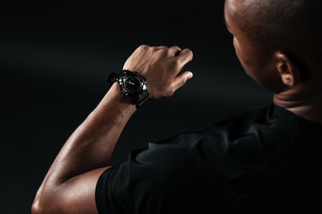 Cortada a imagem do jovem afro-americano, olhando para o relógio