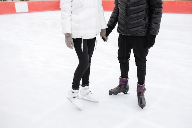 Cortada a imagem do jovem casal apaixonado patinando na pista de gelo