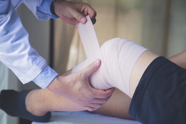 Cortada a imagem do médico aplicar curativo na perna do paciente