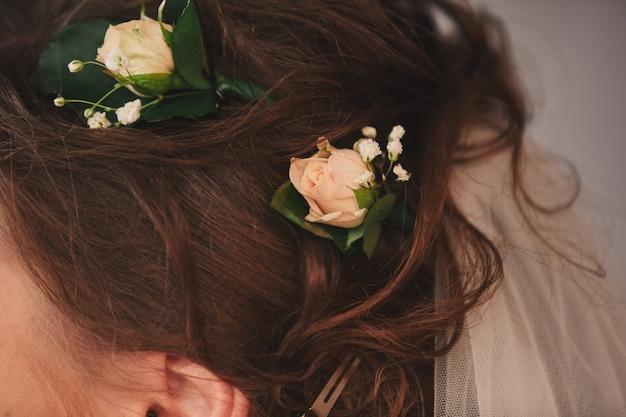 Cortada foto de close-up de cabelo nupcial com flores cor de rosa no cabelo dela. manhã da noiva