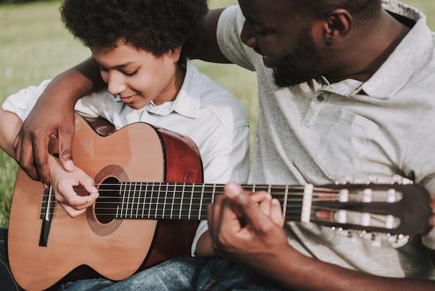 Cortada foto do pai afro mostrando lições para jogar