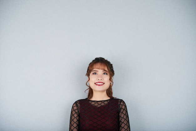 Cortada menina adorável olhando sorrindo em pé na parede cinza