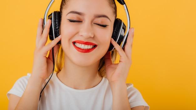 Cortada. menina sorrindo com os olhos fechados, ouvindo fones de ouvido música na cabeça, vestida com uma camisa branca, estado emocional positivo