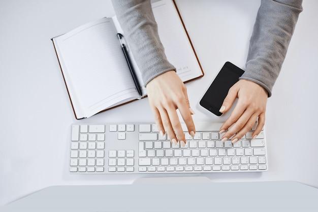 Cortada o retrato das mãos de mulher, digitando no teclado e trabalhando com computador e gadgets. freelancer feminino moderno, projetando um novo projeto para a empresa, fazendo anotações no caderno e smartphone