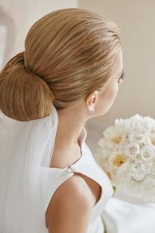 Cortada o retrato de uma jovem mulher com cabelos loiros e penteado de casamento