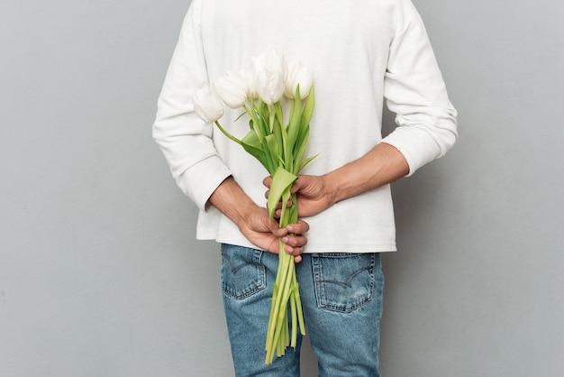 Cortada para trás ver foto de jovem com flores.