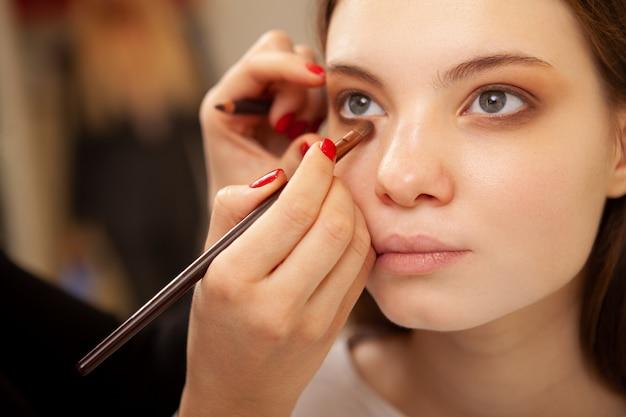 Cortada perto de uma bela jovem, recebendo sua maquiagem feita pelo maquiador profissional