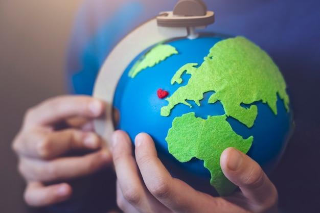 Cortada tiro menino segurando a terra nas mãos. mãos segurando o globo com coração vermelho no mapa, dia da terra em 22 de abril, conceito de dia de ambiente mundo verde